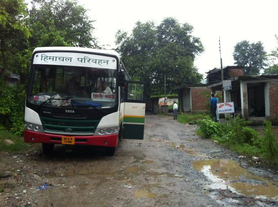 インドの村で大雨で寸断された道を復旧を待つバス